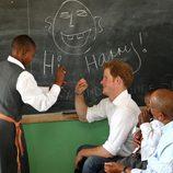 Un niño escribe en la pizarra junto al Príncipe Harry en Lesotho