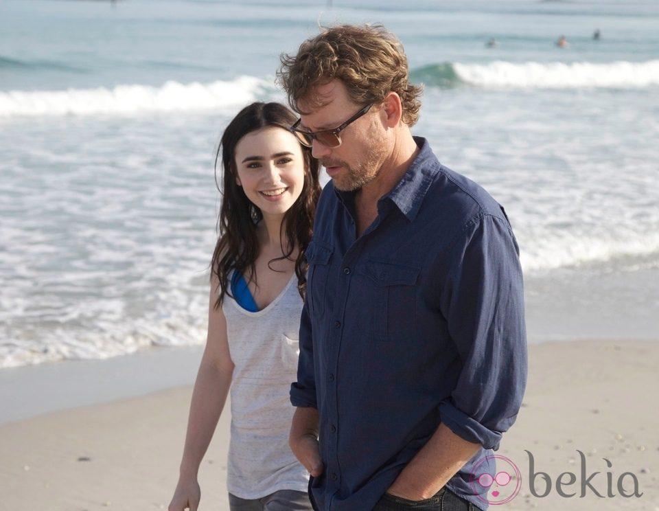 Greg Kinnear y  Lily Collins en una escena de 'Un invierno en la playa'