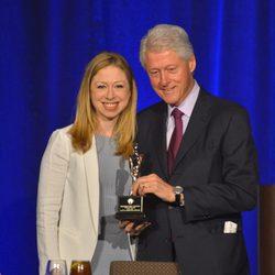 Bill Clinton con su hija Chelsea sosteniendo el galardón a 'Padre del Año'