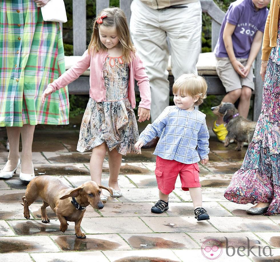 Isabel y Vicente de Dinamarca juegan con un perro durante vacaciones en Gråsten Slot