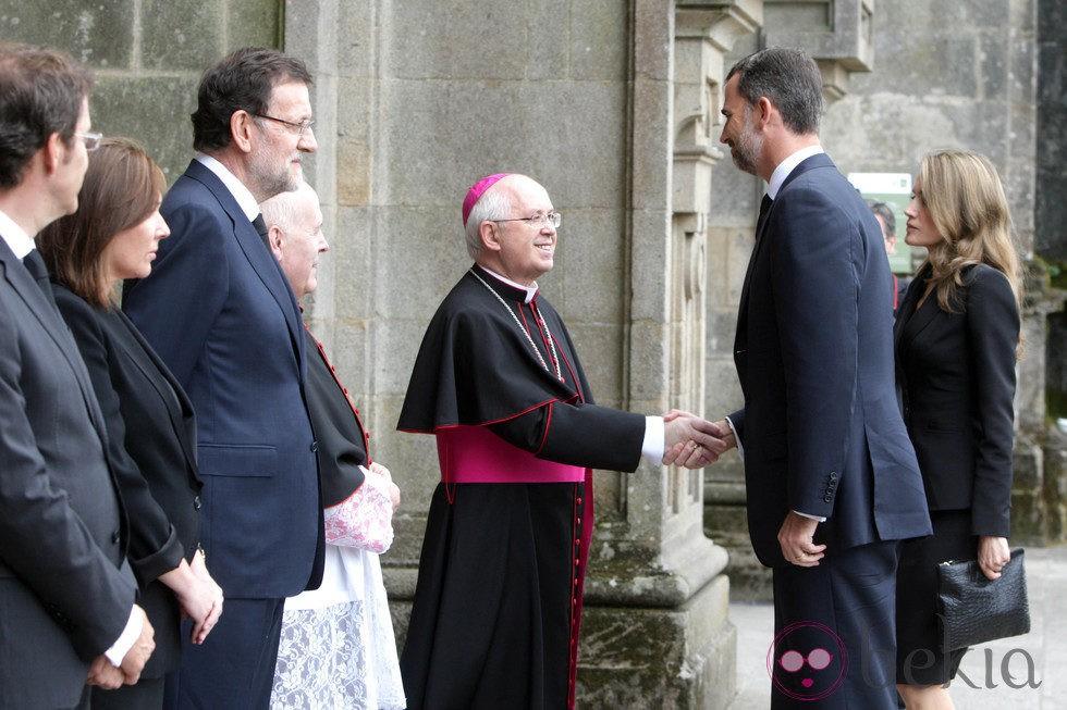 El príncipe Felipe saluda al obispo de Santiago en el funeral por las víctimas del tren de Santiago