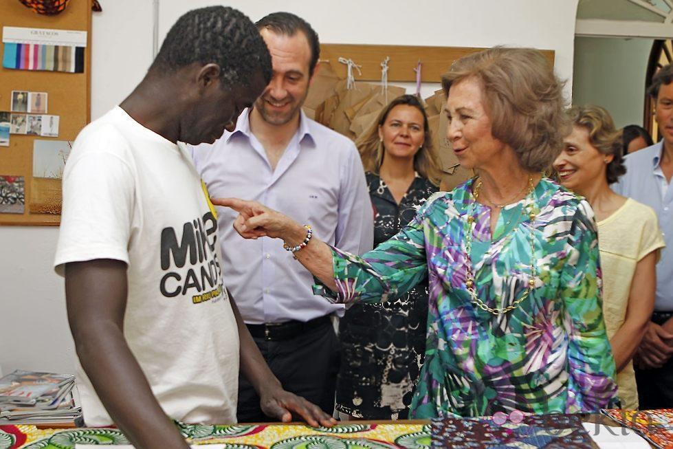 La Reina Sofía toca la camiseta de un miembro del proyecto 'koluté' de Cáritas Mallorca