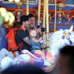 David Beckham con sus hijos Brooklyn y Harper Seven en los caballitos de Disneyland