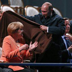 Vladimir Putin cubriendo a Angela Merkel con una manta en San Petersburgo