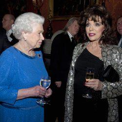 La Reina Isabel charla con Joan Collins en una recepción en Buckingham Palace