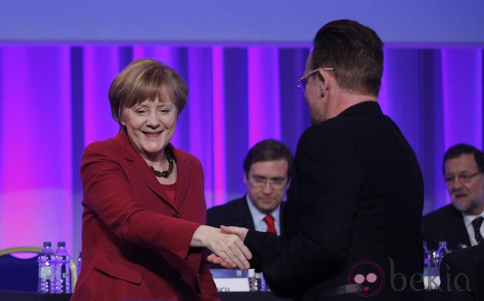Bono saluda a Angela Merkel durante su intervención en el congreso del Partido Popular Europeo en Dublín