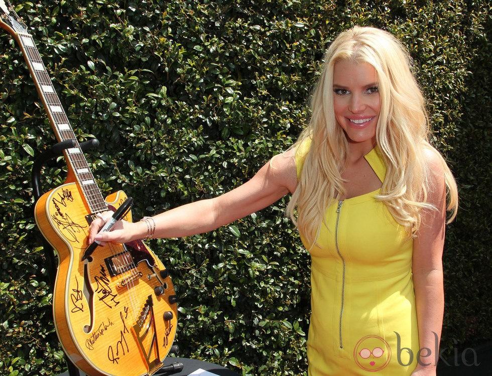 Jessica Simpson firma una guitarra en el evento benéfico de John Varvatos