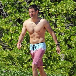 James Marsden en bañador caminando por una playa de Hawaii