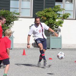 Haakon de Noruega jugando al fútbol en un partido amistoso