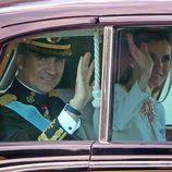 El Rey Felipe VI y la Reina Letizia saludan durante el recorrido hasta el Congreso de los Diputados