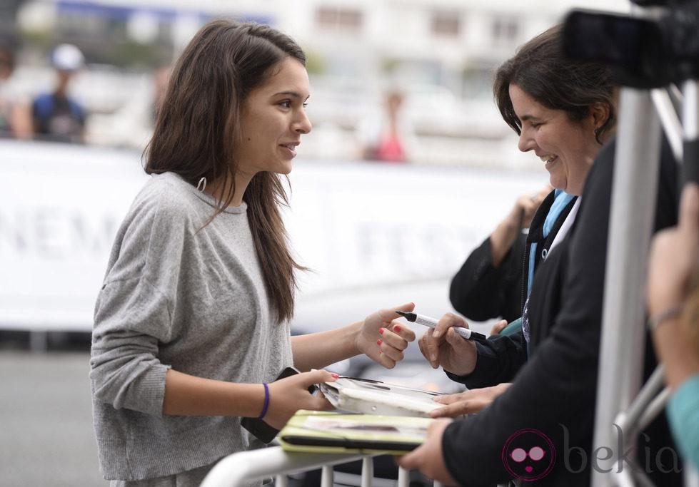 Claudia Traisac atendiendo a sus fans a su llegada al Festival de San Sebastián 2014
