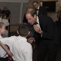 El Principe Guillermo con unos niños en la cena benéfica SkillForce