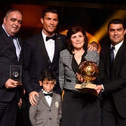 Cristiano Ronaldo posando con el Balón de Oro 2014 junto a su familia