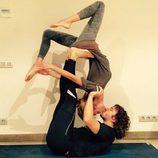 Carles Puyol y Vanesa Lorenzo practicando acroyoga mientras se dan un beso