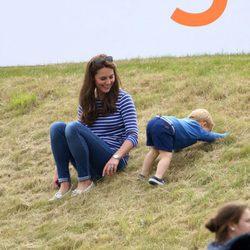 El Príncipe Jorge de Cambridge jugando en el césped junto a Kate Middleton