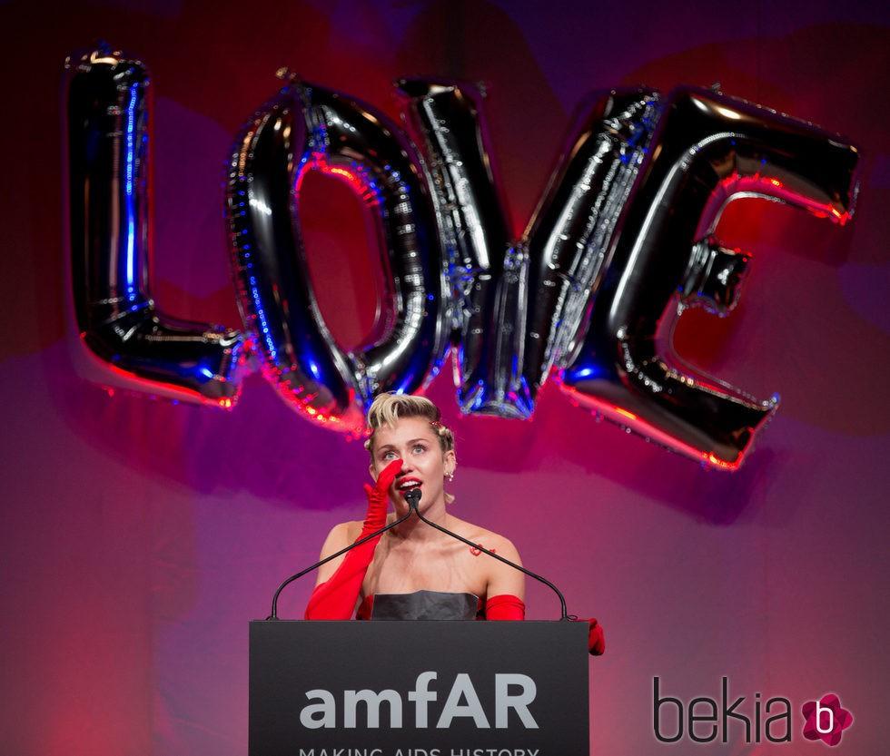 Miley Cyrus muy emocionada recogiendo su premio en la gala amfAR Inspiration de Nueva York 2015