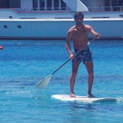 El novio de Irene Carbonero con el torso desnudo practicando paddle surf