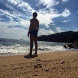 Andrés Velencoso en bañador mirando al mar desde una playa