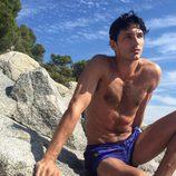 Andrés Velencoso con el torso desnudo sobre una roca