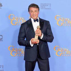 Sylvester Stallone posando con su premio en los Globos de Oro 2016