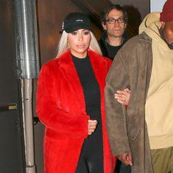 Kim Kardashian con un jumpsuit negro con un abrigo rojo