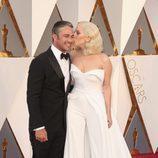 Lady Gaga besando a su prometido Taylor Kinney en la alfombra roja en los Premios Oscar 2016