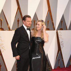 Kate Winslet observa de forma cariñosa a Leonardo DiCaprio en la alfombra roja de los Premios Oscar 2016