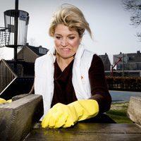 La Reina Máxima de Holanda limpiando una plataforma de madera