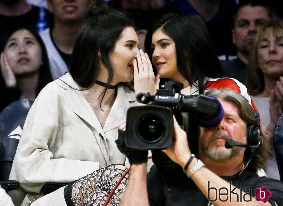 Kendall y Kylie Jenner compartiendo confidencias en un partido de la NBA