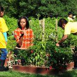 Michelle Obama junto a dos niños en la recogida de la cosecha en la Casa Blanca