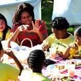 Michelle Obama charla mientra come con unos niños tras recoger la cosecha en la Casa Blanca