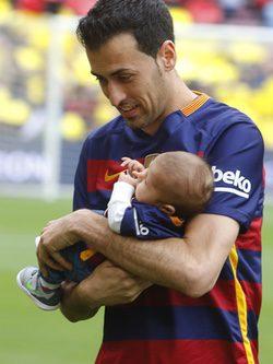 Sergio Busquets con su hijo Enzo en brazos en el Camp Nou