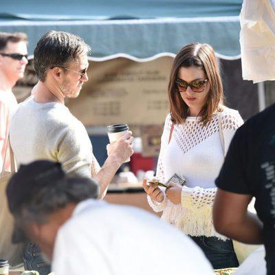 Anne Hathaway, con unos billetes, y Adam Shulman en un mercado de Los Ángeles
