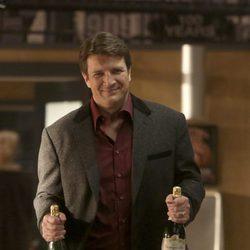 Nathan Fillion con dos botellas de champán en la octava temporada de 'Castle'