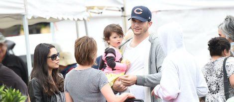 Mila Kunis, Ashton Kutcher y su hija Wyatt charlando con unos conocidos