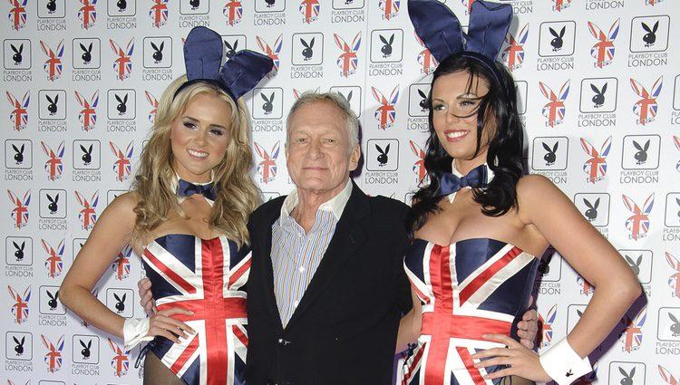 Hugh Hefner posando en un photocall junto a dos conejitas Playboy