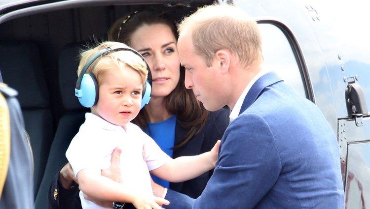 Los Duques de Cambridge y su hijo Jorge de Cambridge bajando de un helicóptero