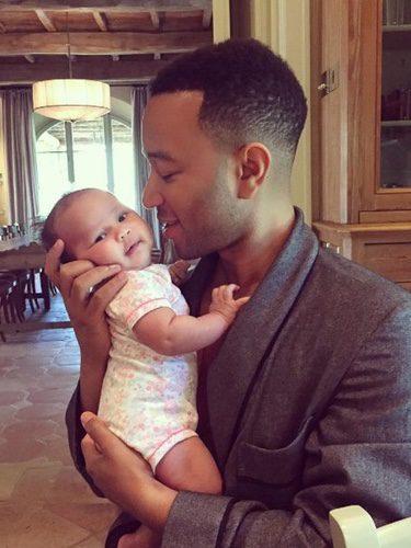 John Legend sosteniendo cariñosamente a su hija Luna