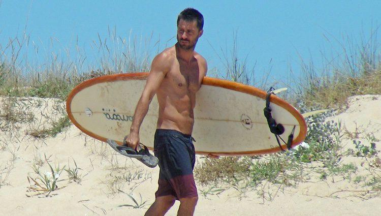 Hugo Silva con el torso desnudo y una tabla de surf