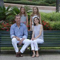 Los Reyes Felipe VI y Letizia con sus hijas en un banco de los jardines de Marivent