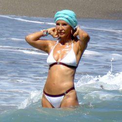 Carmen Lomana muy chic con un bikini blanco y un turbante turquesa en Marbella