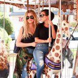 Kourtney Kardashian y Khloe Kardashian montando en un tiovivo en California