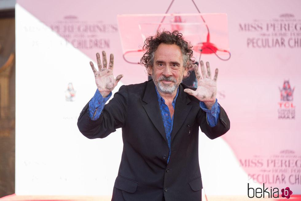 Tim Burton motrando sus manos tras dejar sus huellas frente al Teatro Chino de Hollywood